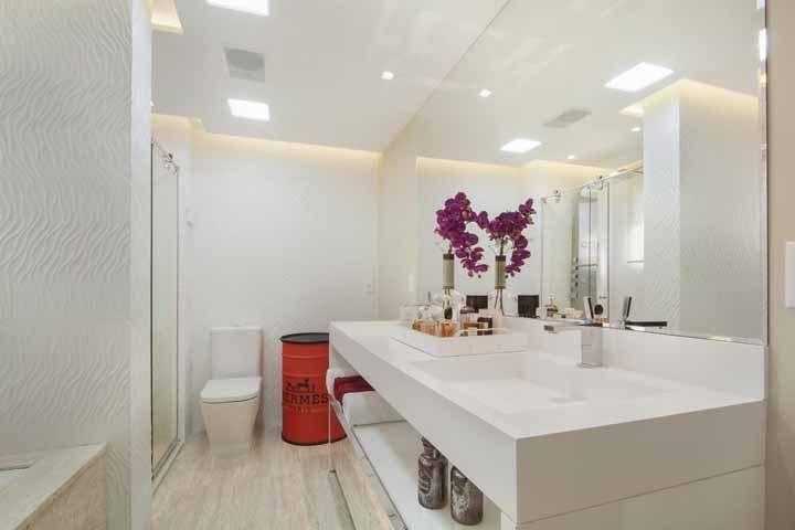 Esse banheiro branco e todo elegante é completo, não precisava de mais nada, mas é impossível negar a influência positiva que o tambor vermelho exerce sobre ele