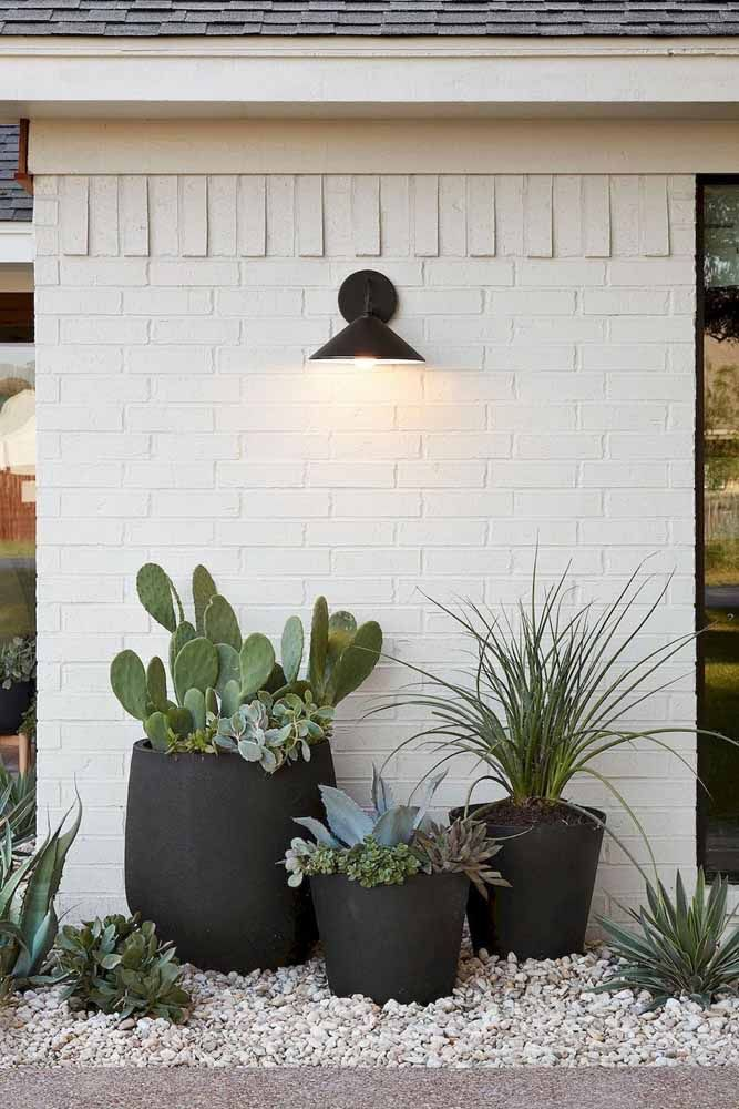 A parede de tijolinhos branca foi destaca pelos três vasos grandes pretos recheados de cactos e suculentas