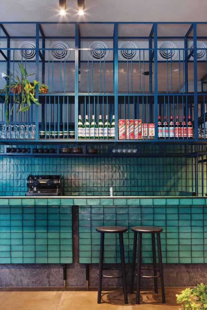 Nesse bar, o verde água está presente nos azulejos de metro; para completar o cenário, grades azuis
