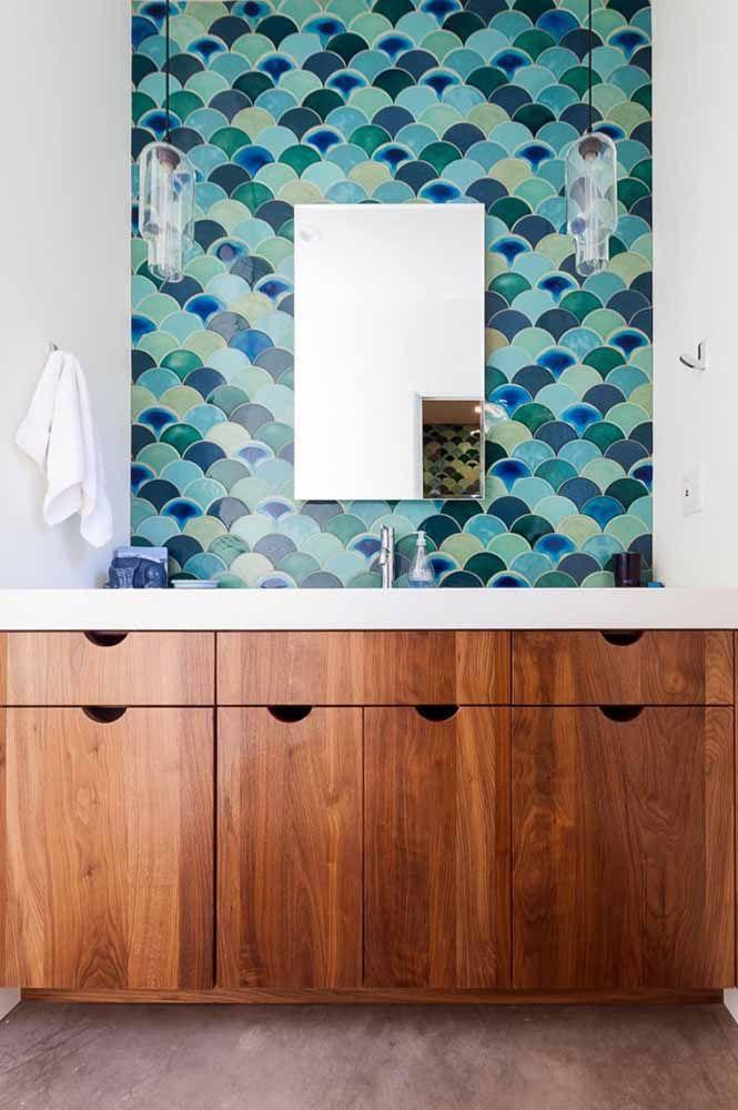 Um painel feito em diferentes tons de verde e azul decora a bancada desse banheiro