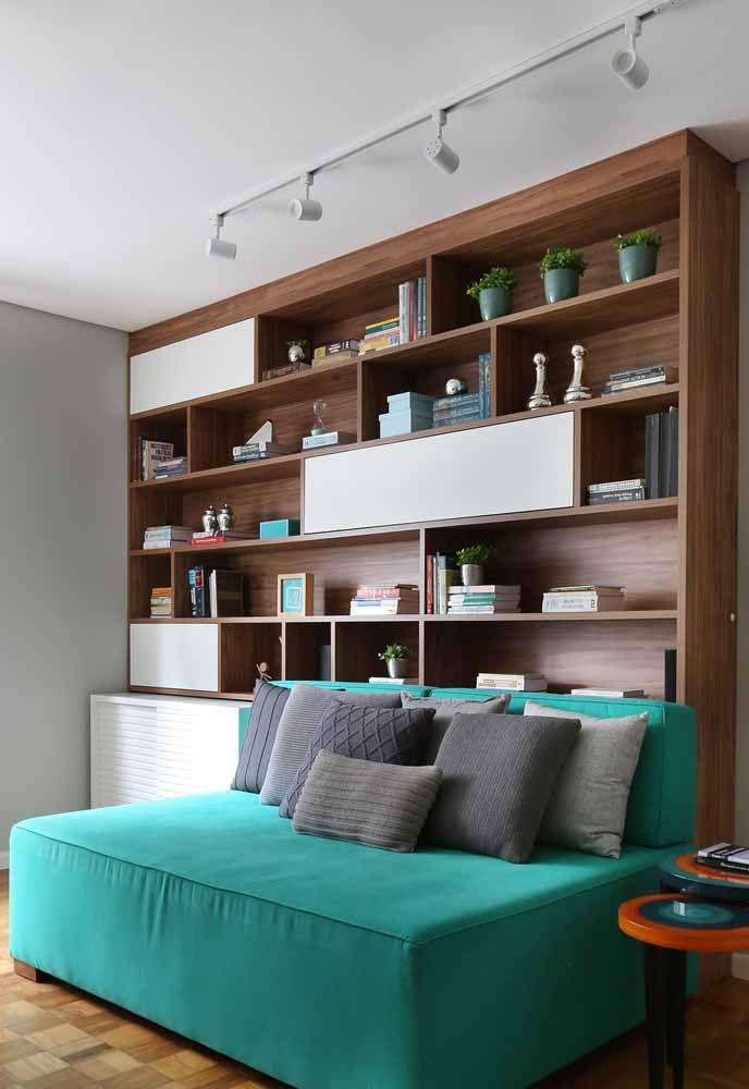 Verde água no sofá e nos detalhes da estante