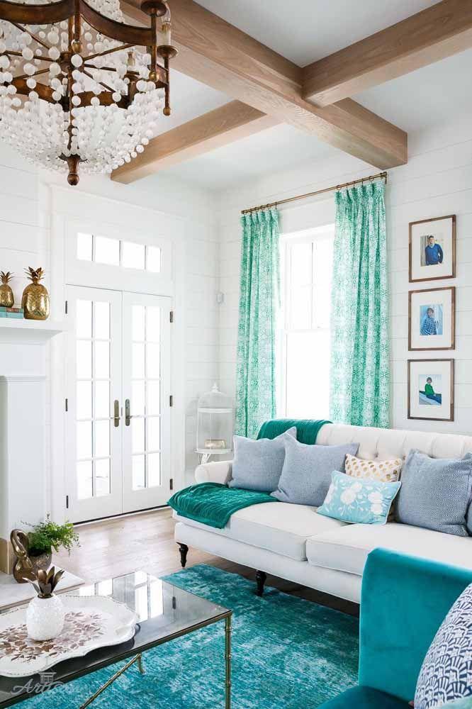 A iluminação natural e o frescor do verde água trazem um clima acolhedor e receptivo para essa sala que mescla uma decor rústica com uma proposta de viés clássico