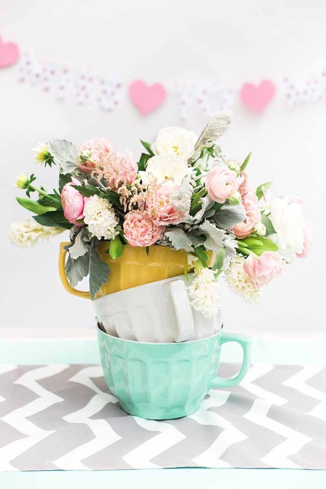 Trio de xícaras coloridas com algumas flores e você já tem um arranjo temático para o chá