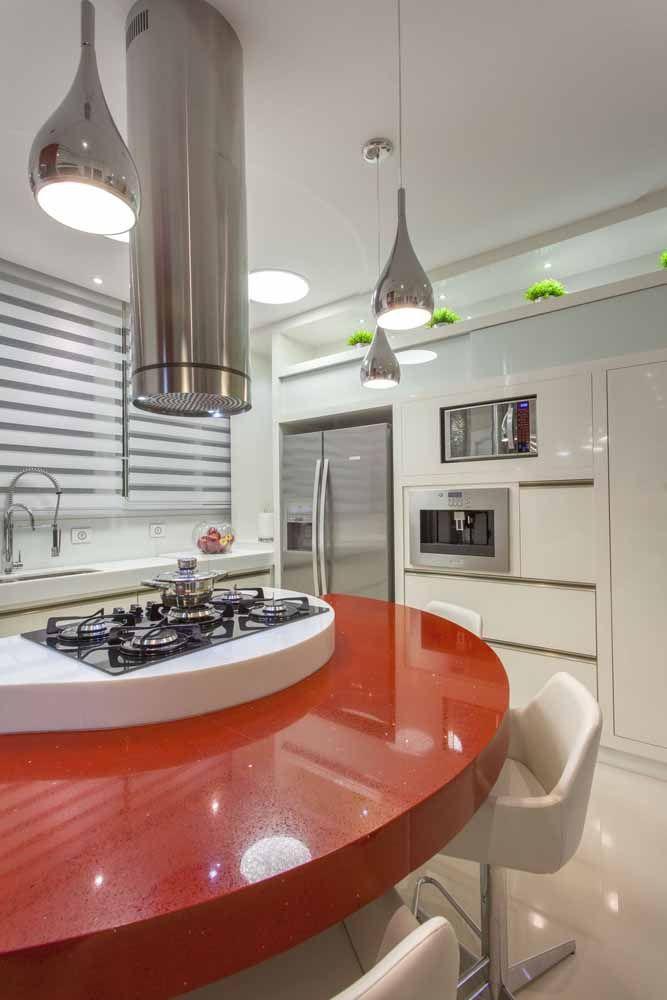 Não é só no formato que essa bancada chama a atenção; a pedra de Silestone vermelho stellar é puro luxo para a cozinha.