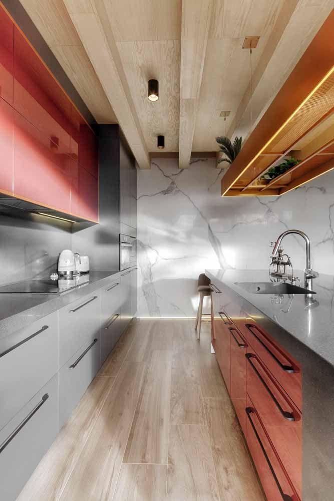 Cozinha cinza e vermelha apostou no contraste entre a bancada de Silestone e a parede de mármore