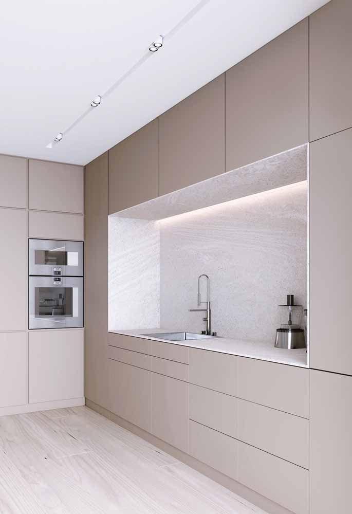Para deixar a cozinha ainda mais uniforme, a Silestone branca foi usada em toda a bancada e, ainda, como revestimento da parede