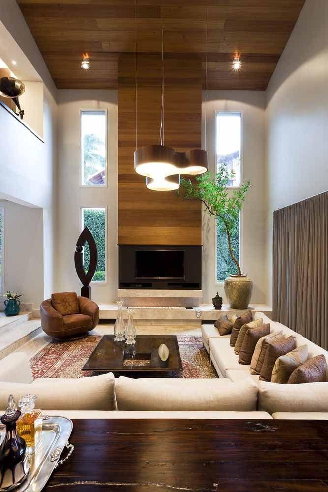 Muitas almofadas, um vaso de bambu mosso e uma bela obra de arte compõe a decoração dessa grande sala de estar