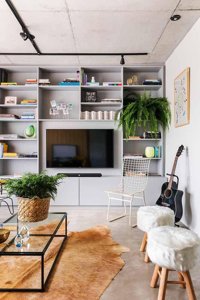 Uma estante até o teto, vasos de plantas e texturas macias no tapete e nos bancos : essa é a receita para tornar essa sala mais receptiva