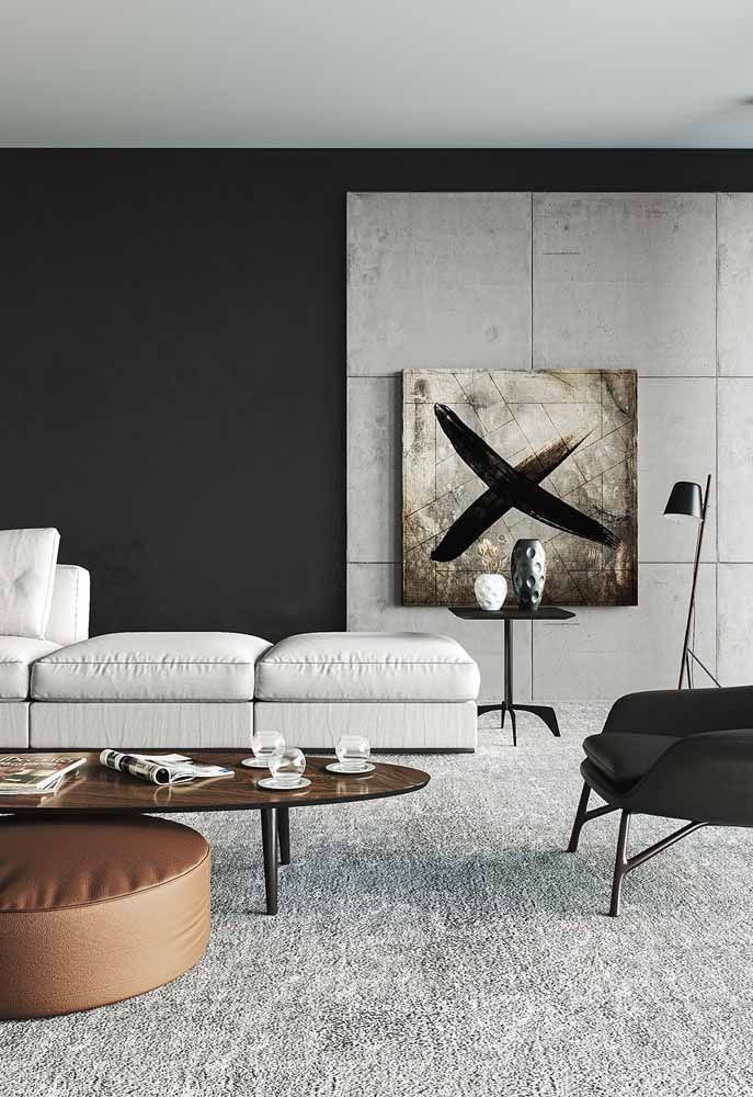 O truque para deixar essa sala mais aconchegante foi pintar a parede de preto e usar um tapete que cobre todo o chão