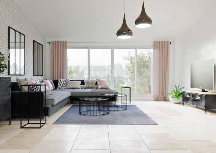 Já essa sala de estar grande, que mescla o escandinavo com o industrial, apostou em um sofá de canto e em uma cortina rosa para preencher o espaço