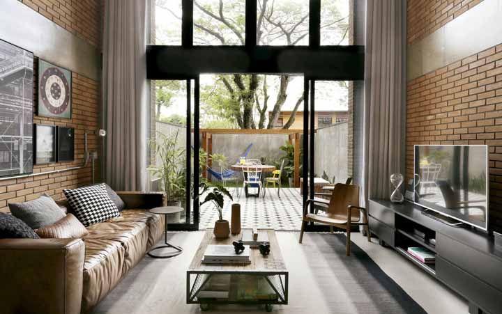 Já nessa outra sala, a mesinha de centro ajuda a diminuir visualmente a distancia entre o sofá e a TV