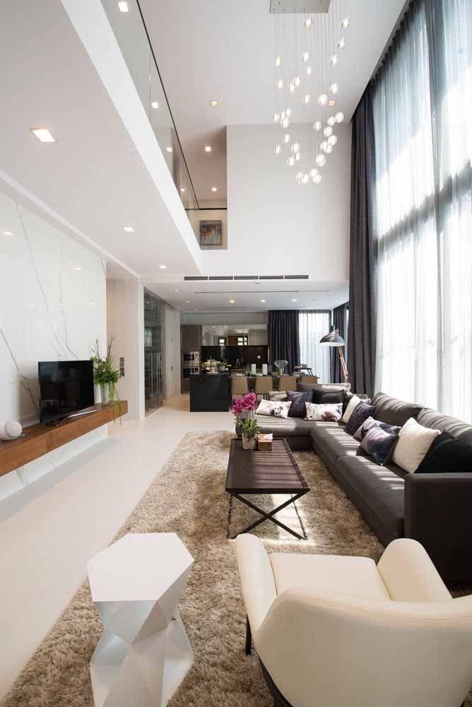 Aqui, a mobília acompanha o formato retangular da sala; destaque para o lustre pendente