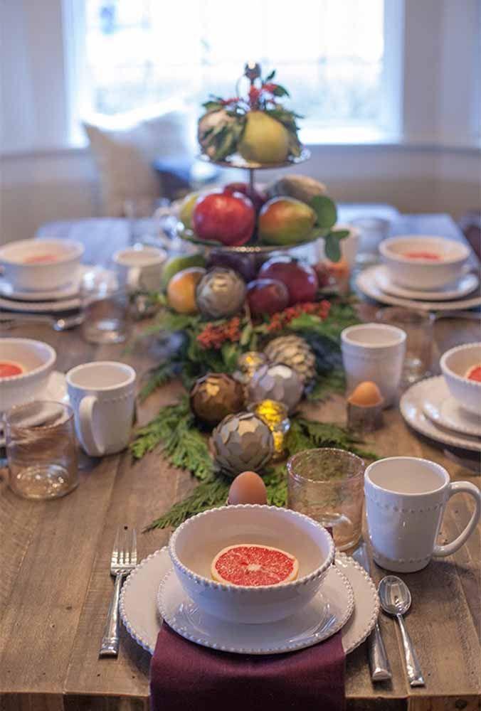 Que tal fazer um arranjo para o centro de mesa usando frutas, bolas diferentes e folhas?