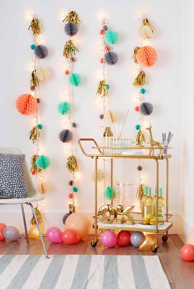 Ao invés de decorar o teto, faça uns arranjos coloridos para pendurar na parede