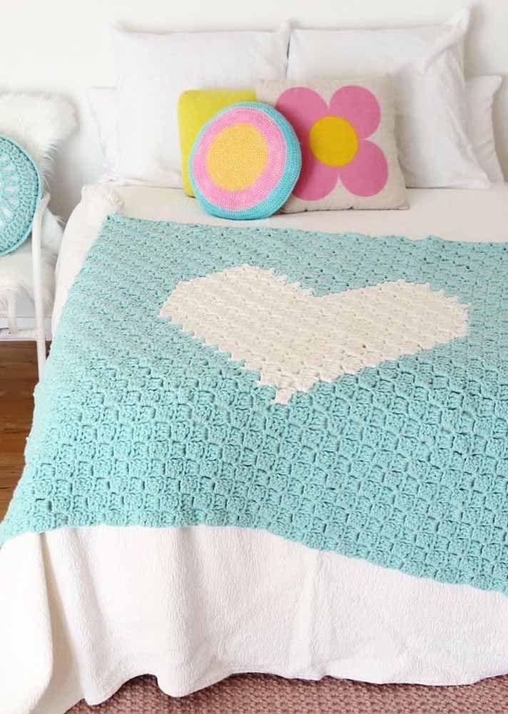 No quarto todo branco, a manta azul celeste de crochê se destaca