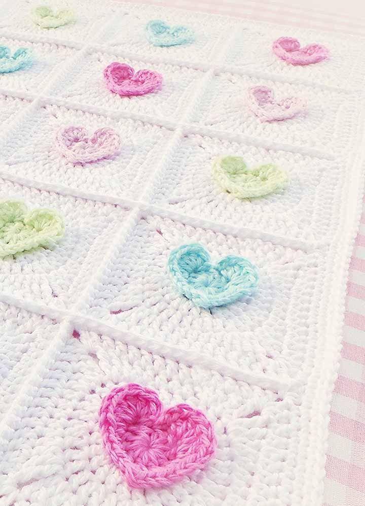 Corações coloridos sobre a manta branca de crochê: uma delicada combinação