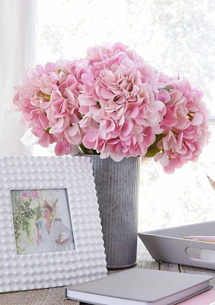 Em meio ao branco e cinza da decoração, um vaso de hortênsias rosas que ninguém suspeita que são artificiais