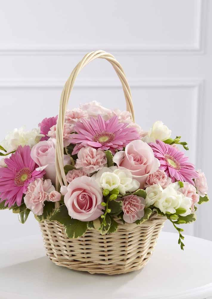O cesto de vime carrega gérberas e rosas artificiais
