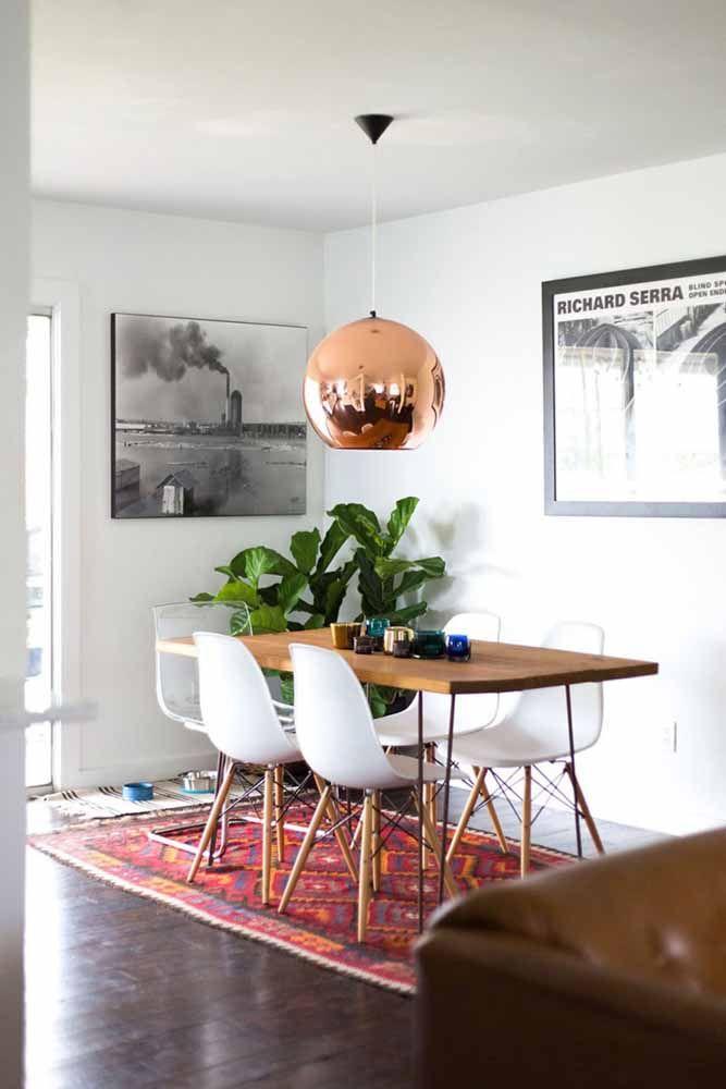 Unindo o clássico ao moderno: é isso que essa sala de jantar faz ao combinar piso de madeira, sofá de couro e tapete persa com cadeiras, mesas e quadros de estilo industrial