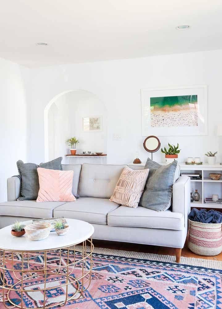 O sofá marrom até tenta marcar o ambiente de sobriedade junto com o tapete persa, mas os detalhes em rosa não deixam