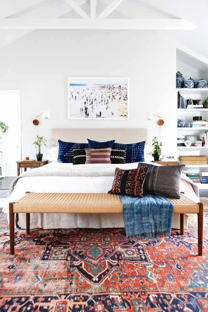 Nesse quarto, as almofadas combinam impecavelmente com o tom de azul do tapete persa