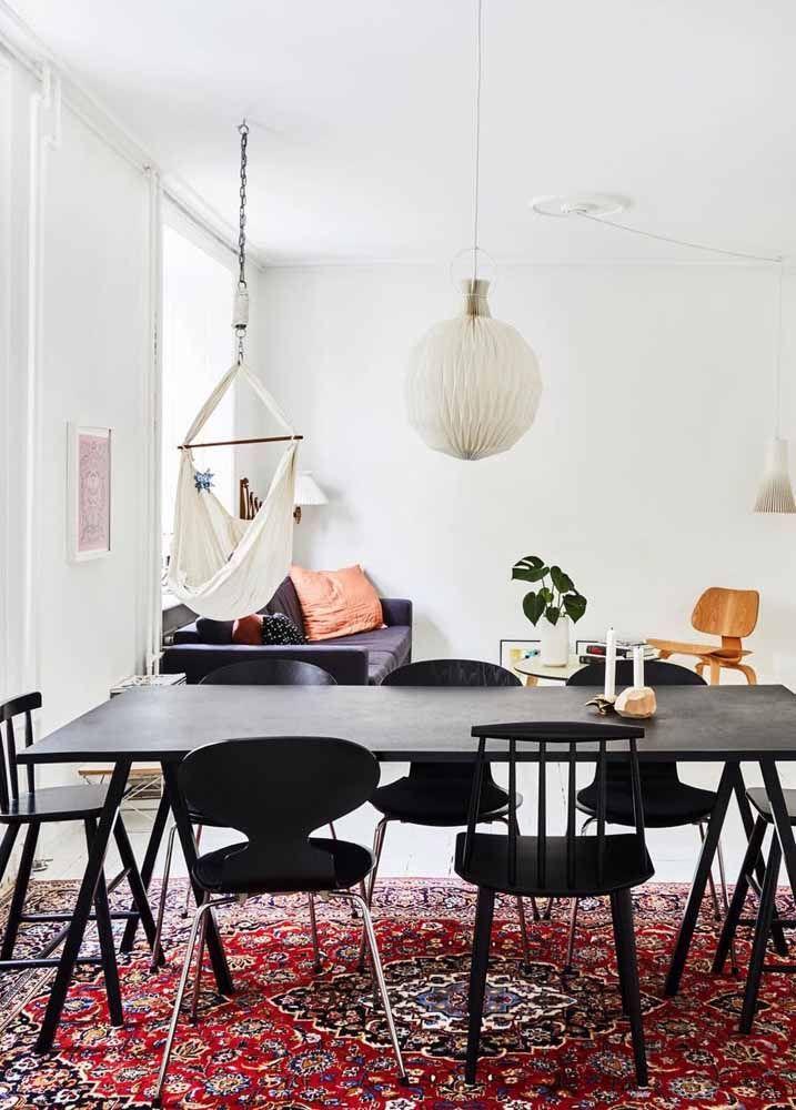 Mesa e cadeiras de jantar pretas sobre o tapete persa vermelho: uma combinação de arrasar