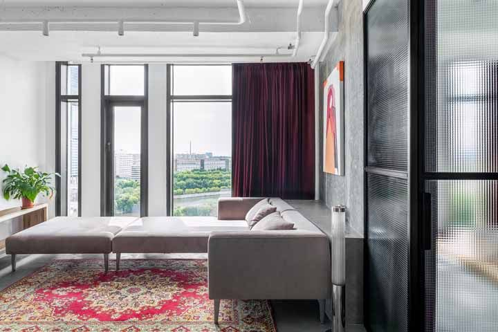 Essa decoração industrial preza pelo conforto visual e sensorial ao apostar na cortina de veludo e no tapete persa