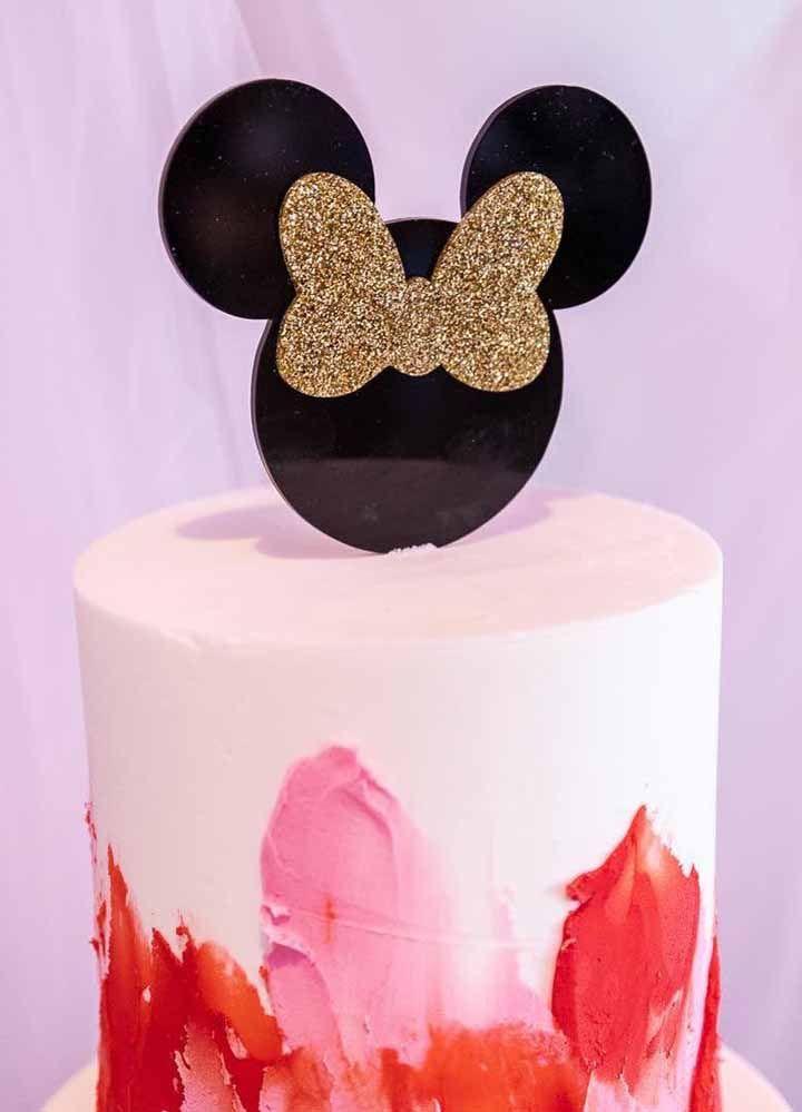Bolo espatulado com as cores da personagem; no topo do bolo a Minnie aparece com um brilhante laço dourado
