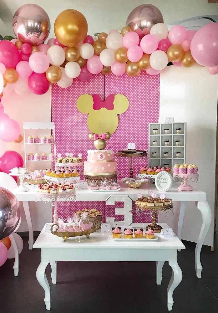 Uma mesa branca entre o rosa e o dourado da decoração