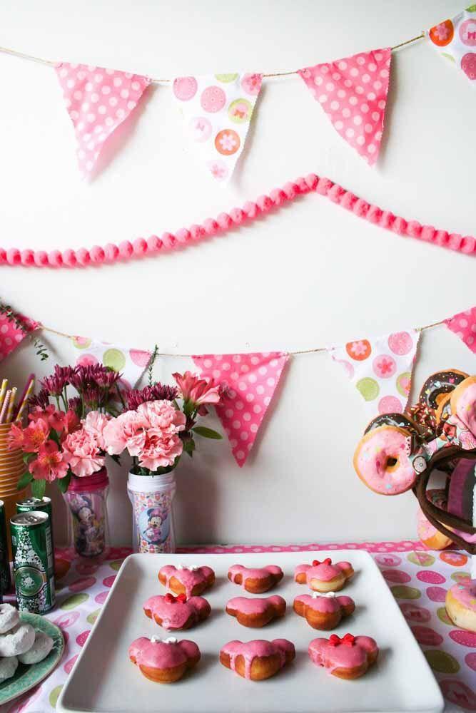 Bandeirolas e flores naturais compõe a decoração dessa festinha Minnie