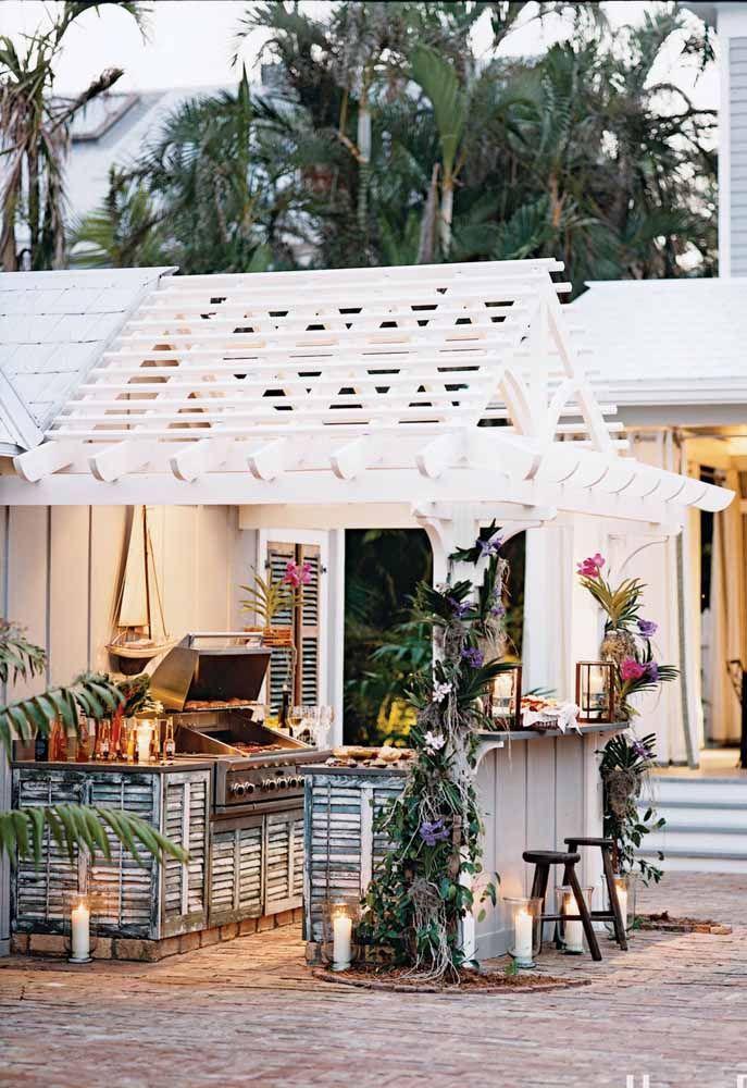 Área de churrasco branca, rústica e com um balcão de madeira pra lá de charmoso