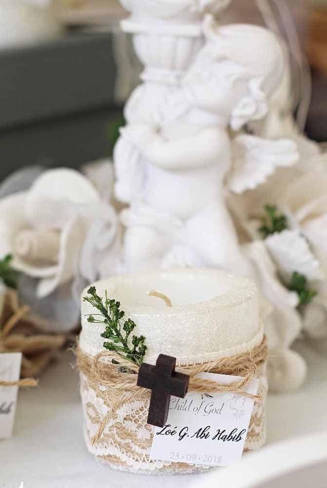 Como transformar uma simples vela branca em lembrancinha de batizado? Usando fita de renda, cisal, galhinho verde e um símbolo cristão