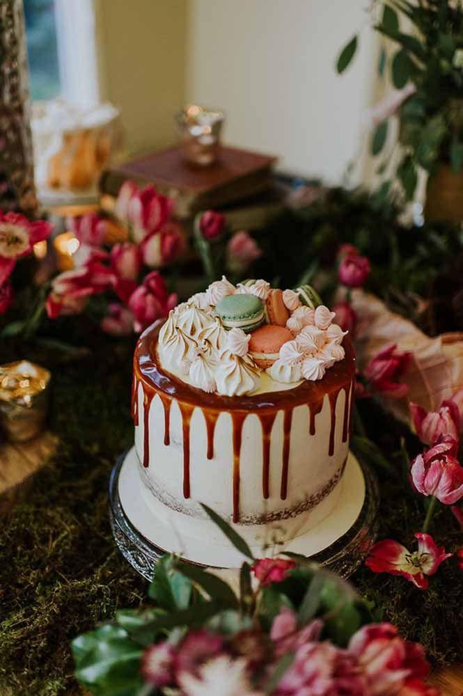 Bolo pequeno e simples, mas decorado com muito capricho e delícias como macarons, suspiros e calda de chocolate
