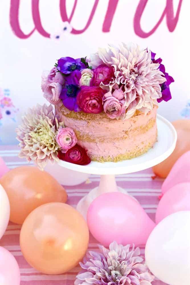 Flores de cores e tamanhos variados enfeitam despretensiosamente esse bolo