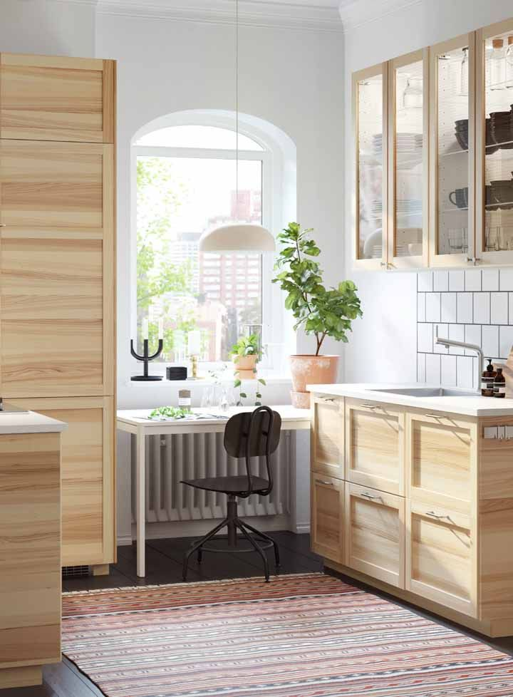 Toda feita com madeira de pinus, essa cozinha modulada ainda traz armários com porta de vidro