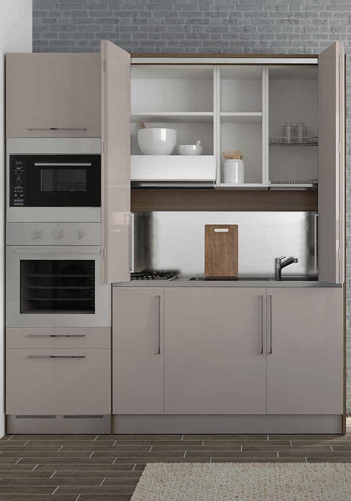 Cozinha modulada com torre quente e sistema de abertura que esconde a bancada da pia e do fogão