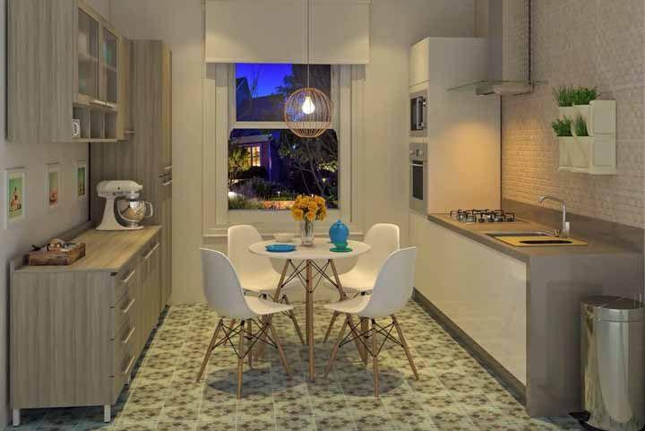 Aqui, a cozinha modulada ocupa os dois lados da parede; no centro, um conjunto de mesa com cadeiras moderno e uma persiana para completar