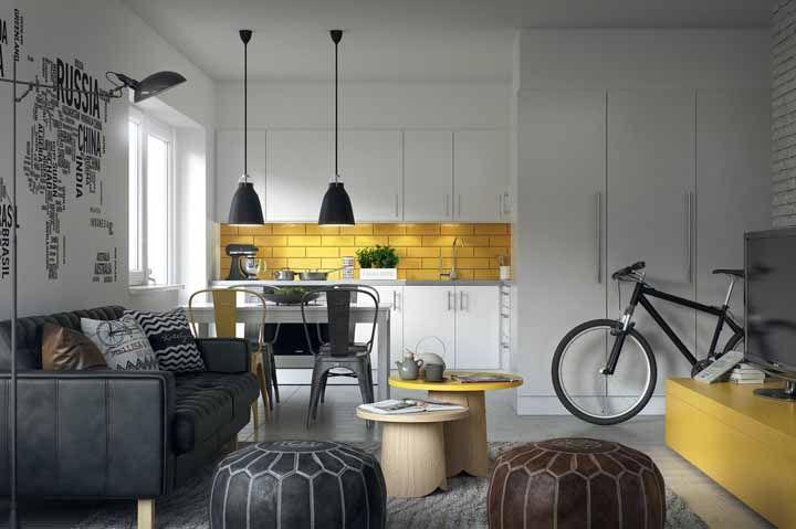 A cozinha modulada branca é vista em todo o ambiente integrado; para relacioná-la com os demais espaços da casa, a ideia foi usar azulejos de metro amarelo combinando com o tom do rack