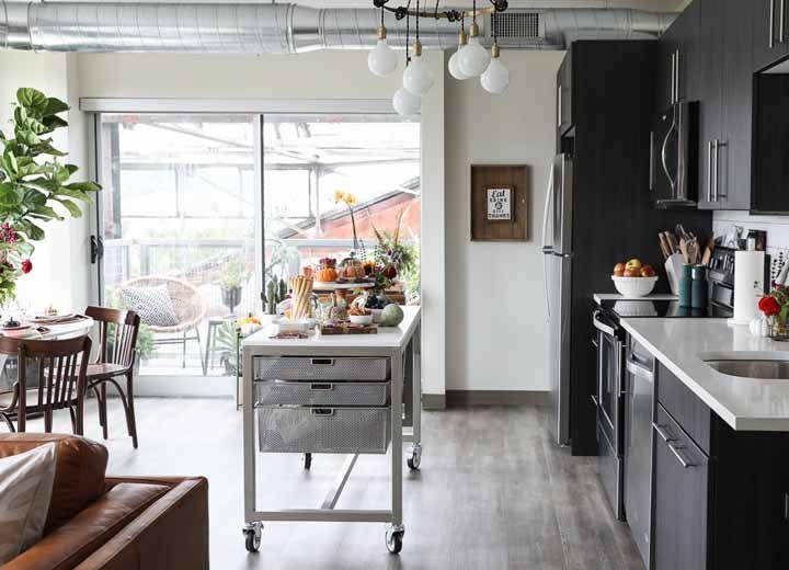 A ilha sobre o carrinho separa a cozinha modulada da sala de estar