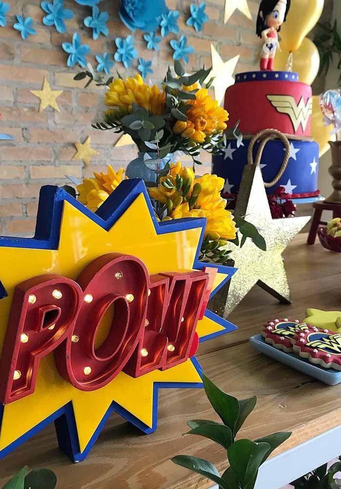 Letreiros iluminados ao melhor estilo HQ; mais ao fundo o bolo decorado com pasta americana traz a personagem em miniatura