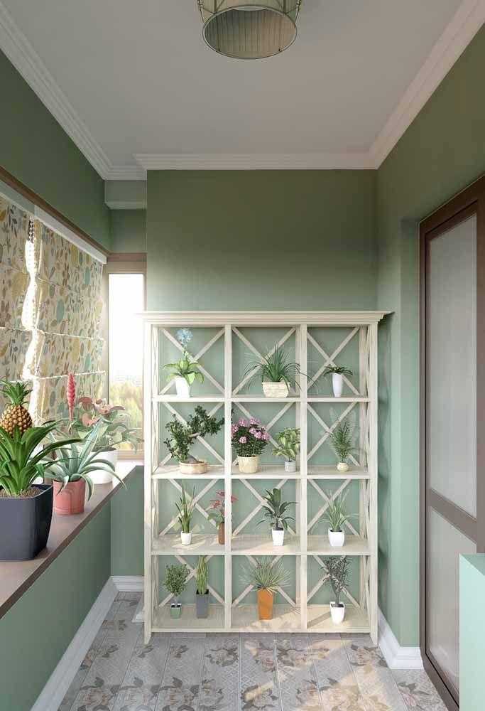 Nessa varanda o jardim suspenso fica em uma estante branca revelando folhagens e espécies floridas