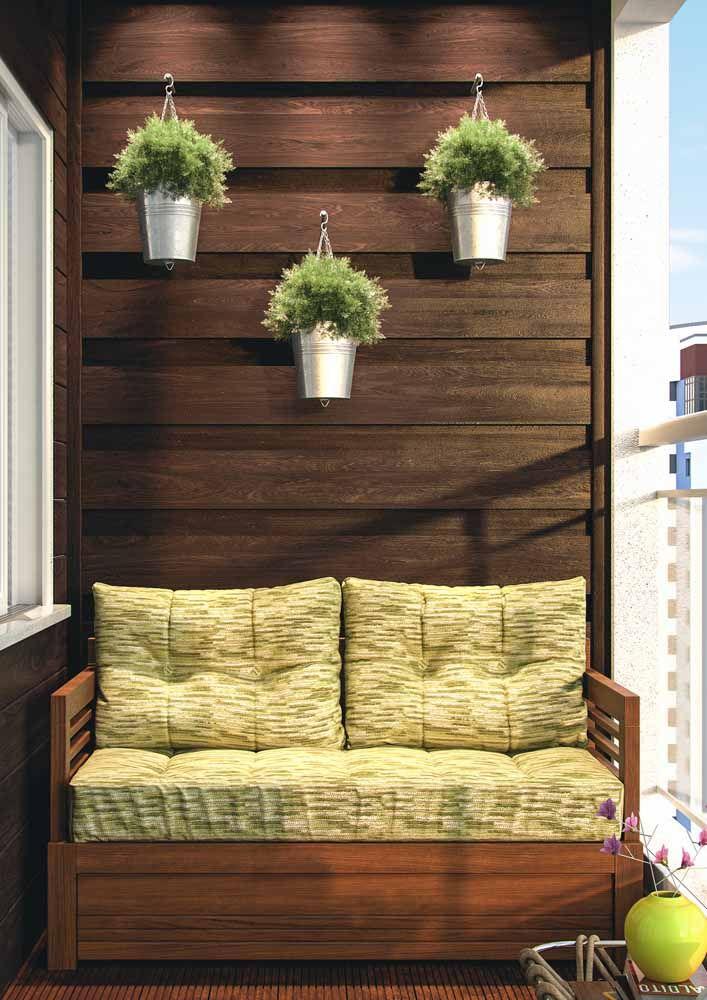 A parede revestida com pallets garante a sustentação de três singelos vasinhos de lata