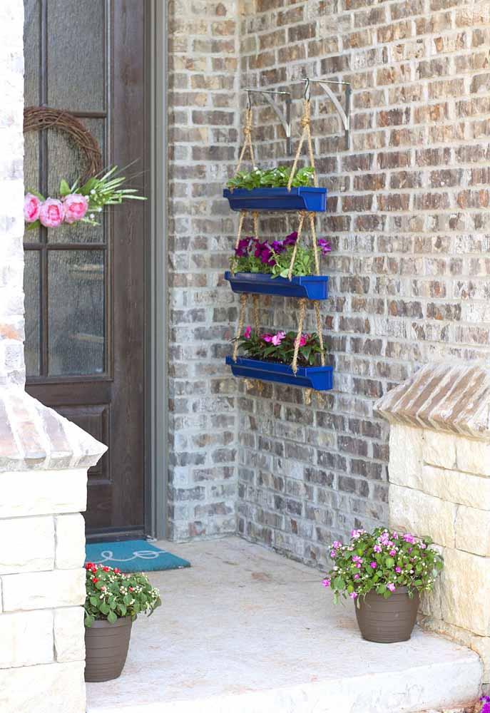O contraste entre a rústica parede de tijolinhos e as jardineiras azuis