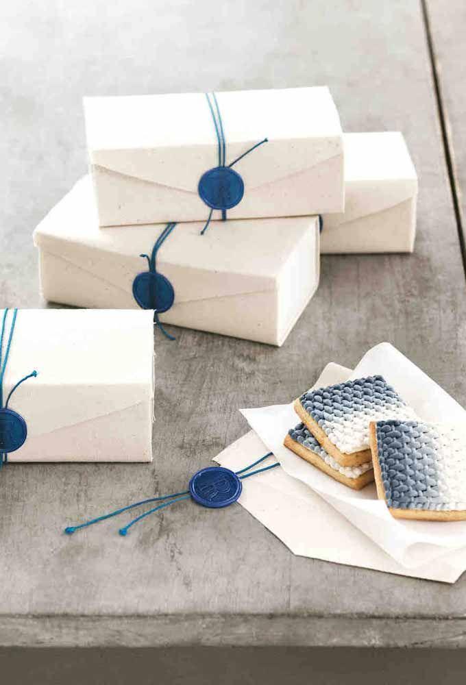 Biscoitinhos decorados oferecidos como lembrancinha de maternidade dentro das caixinhas de papel