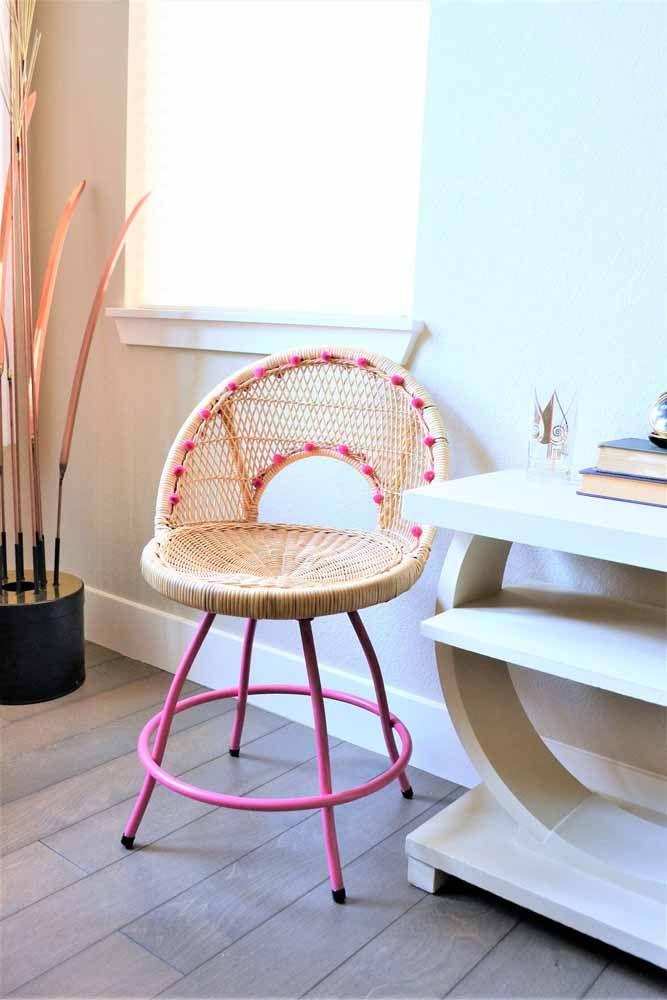 Uma cadeira confortável de vime decorada com mini pompons rosa