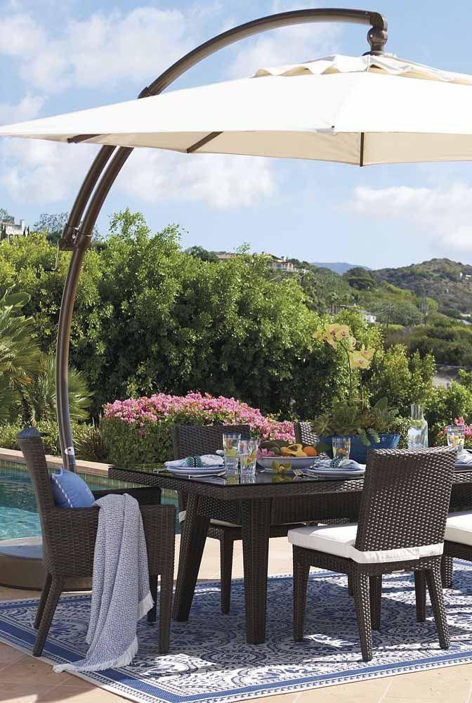 À sombra do ombrelone, um conjunto de mesa e cadeiras de vime sintético