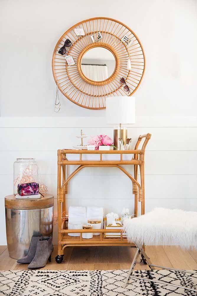 A moldura de vime do espelho funciona como um excelente porta treco; o carrinho de bambu e vime fecha a decor