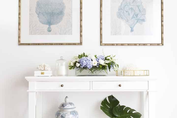 Sobre o aparador, no hall de entrada, um arranjo delicado que mescla flores brancas e hortênsias azuis