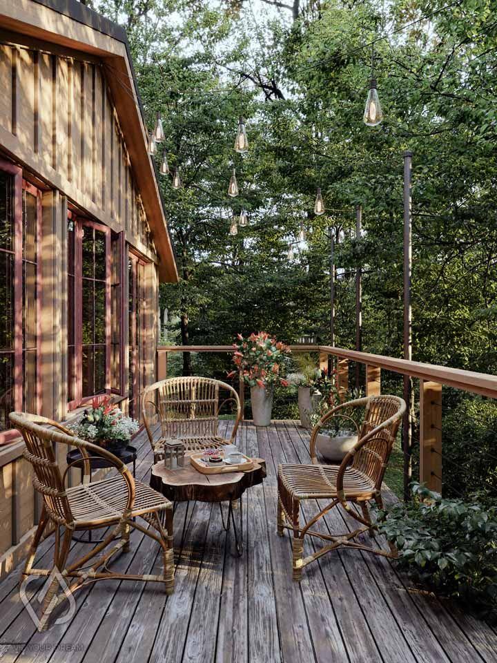 Essa aconchegante e rústica casa de madeira traz um arranjo de chão feito com lírios laranjas