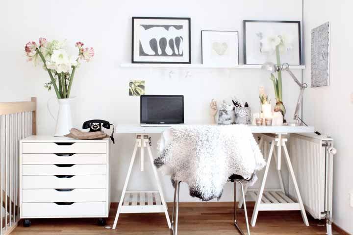 O escritório de estilo escandinavo apostou em duas decorações diferentes com lírios: uma na versão branca com a flor plantada no vaso e outra com lírios de corte em dois tons.